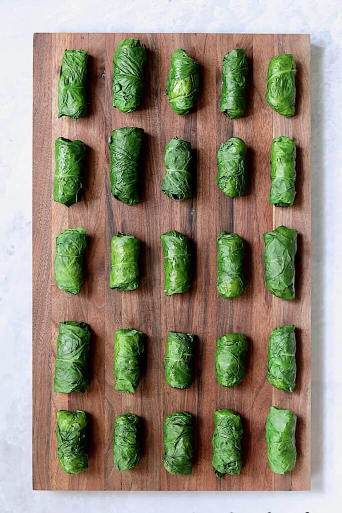 Photo of 25 Quinoa-Stuffed Swiss Chard Dolmas on wood cutting board.