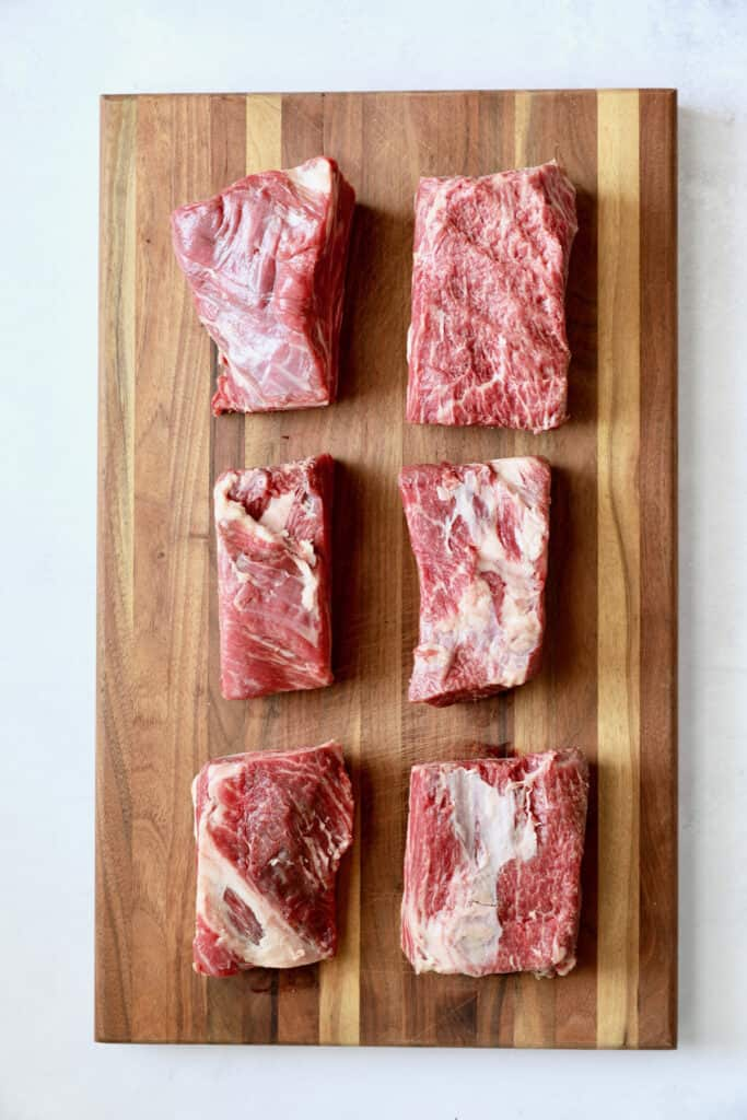 Photo of six uncooked beef short ribs on wood cutting board.