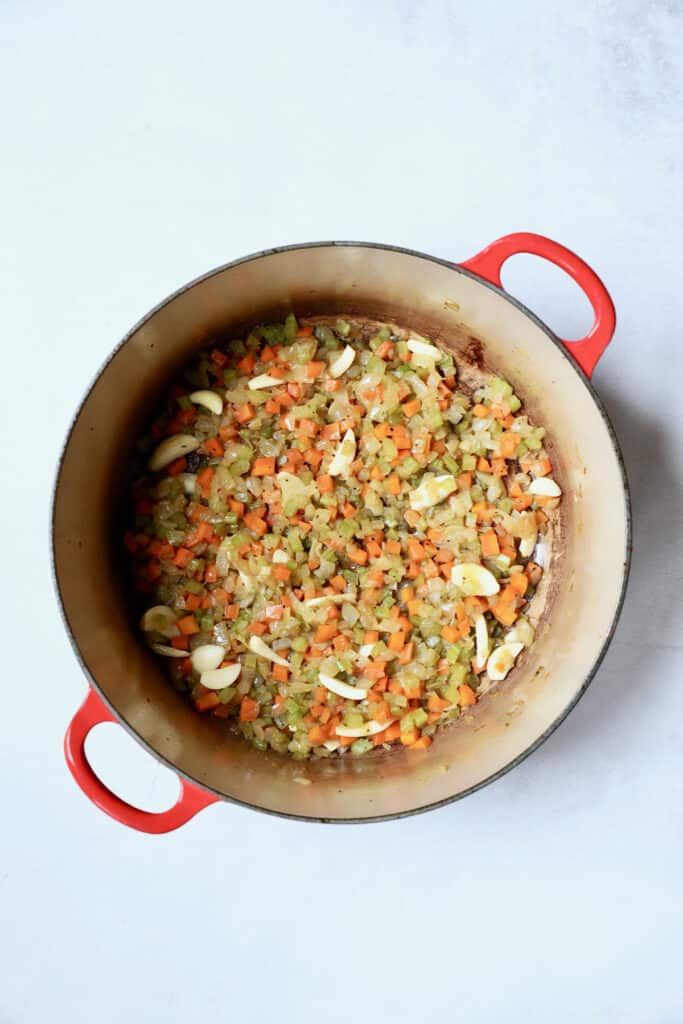 Photo of cooked diced onion, celery, carrot and sliced garlic in red Dutch oven.
