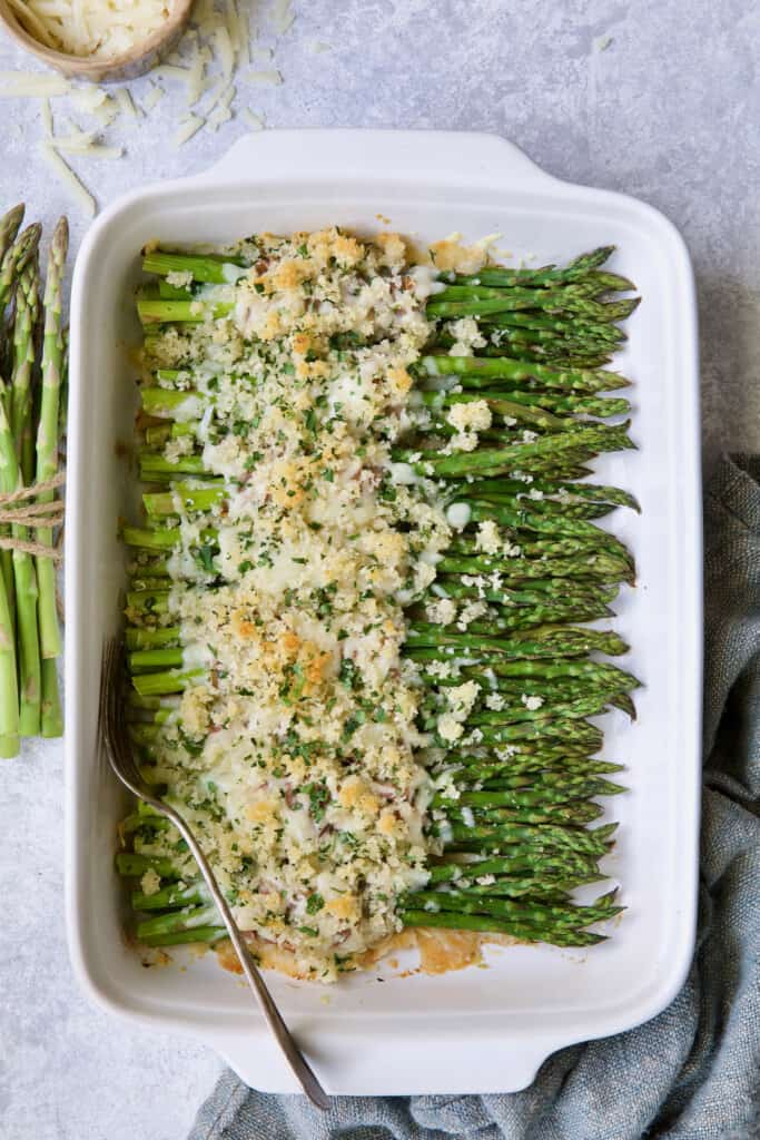 Photo of Asparagus Cordon Bleu in white rectangular baking dish with uncooked asparagus on the side and cheese scattered about.