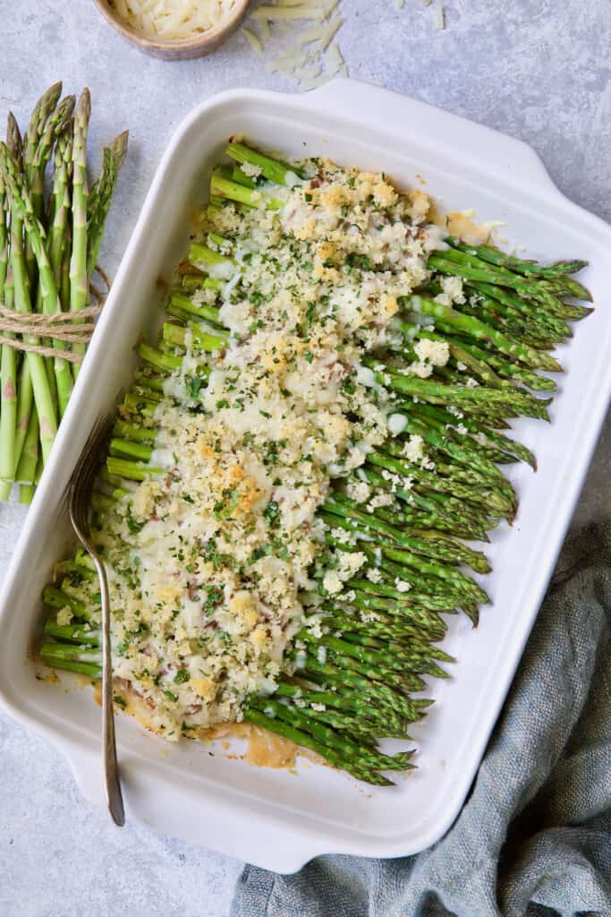 Photo of Asparagus Cordon Bleu in white baking dish on light blue background with cheese scattered about.