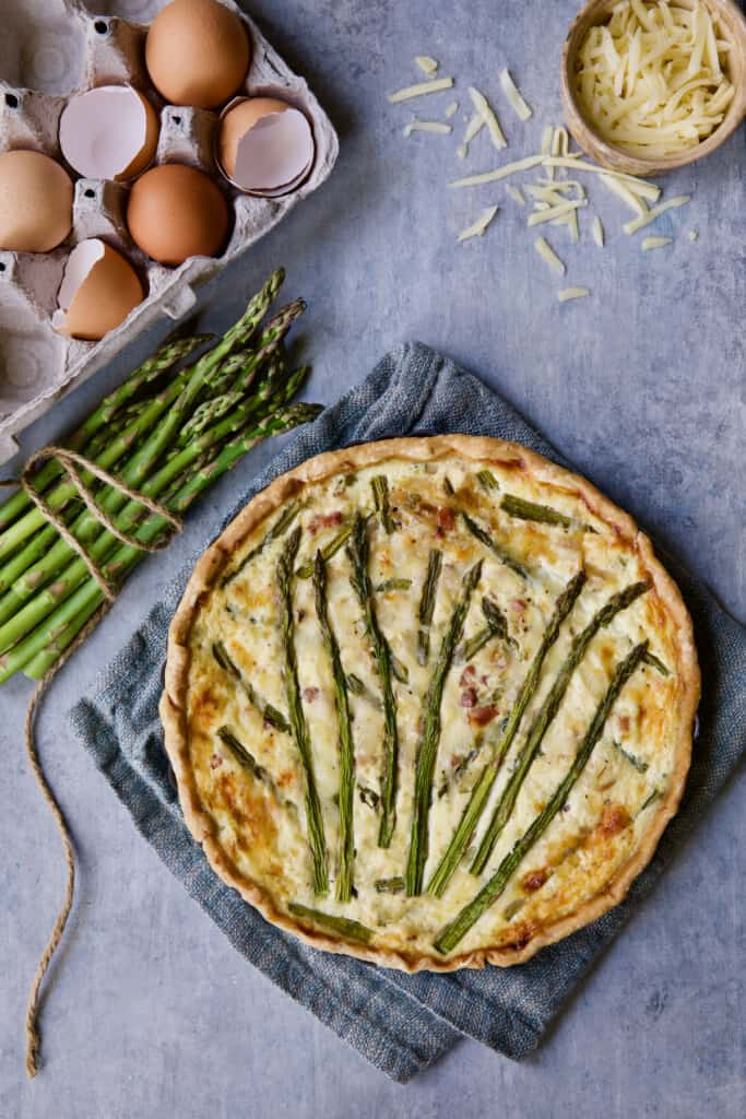 Photo of Asparagus Prosciutto and Fontina Tart with eggs, asparagus and cheese scattered about.
