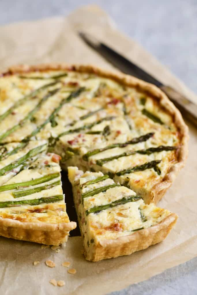 Photo of Asparagus Prosciutto and Fontina Tart on brown parchment paper with three pieces cut.