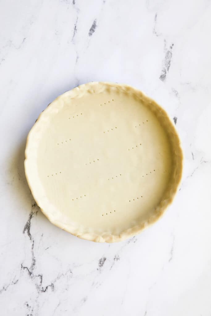 Photo of unbaked pie crust on marble surface.