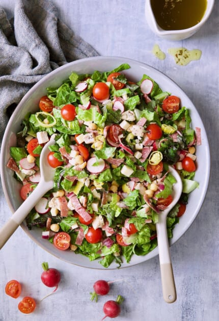 Photo of Italian Chopped Salad with Chicken with tomatoes and radishes scattered around bowl.