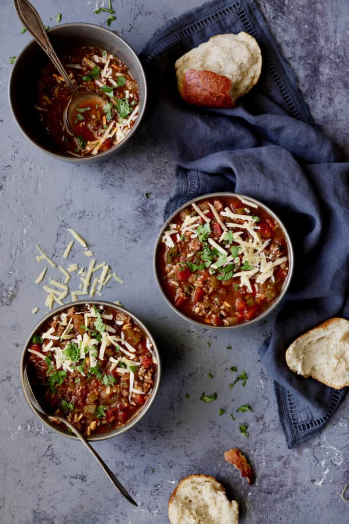 Photo of three bowls of Southwestern Stuffed Pepper Soup in gray bowls topped with cheese and cilantro.