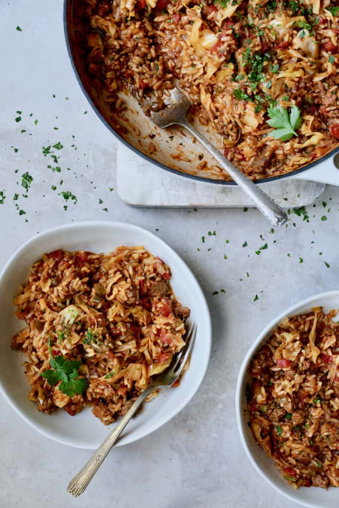 Photo of Unstuffed Chorizo Cabbage Roll Skillet in two serving bowls with some served up from white enamel skillet.