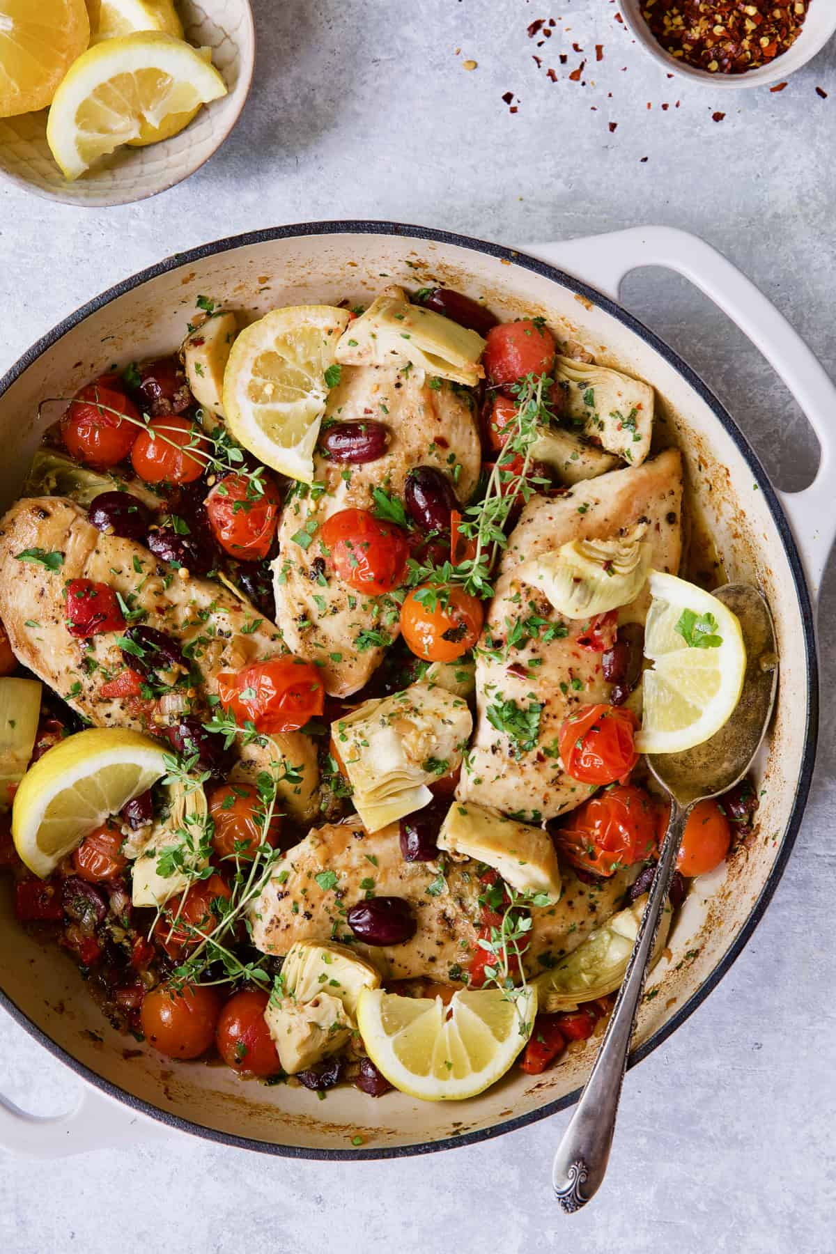 Easy Skillet Mediterranean Chicken in white enamel cast iron skillet garnished with fresh thyme and lemon wedges.