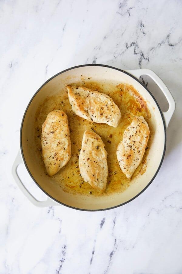 Photo of four boneless skinless chicken breasts in white enamel skillet.