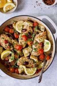 Photo of Easy Skillet Mediterranean Chicken in white enamel cast iron skillet garnished with fresh thyme and lemon wedges.