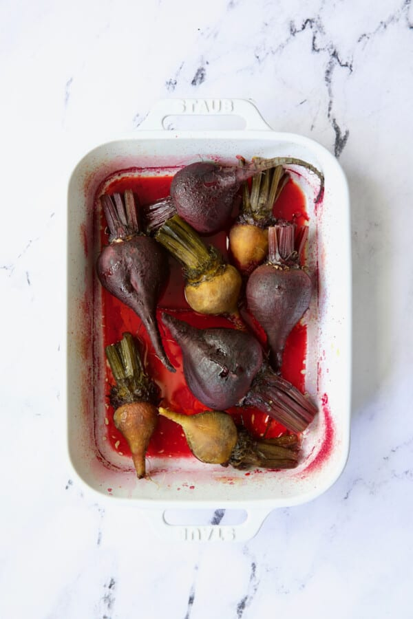 Photo of roasted red and yellow beets in white baking dish.