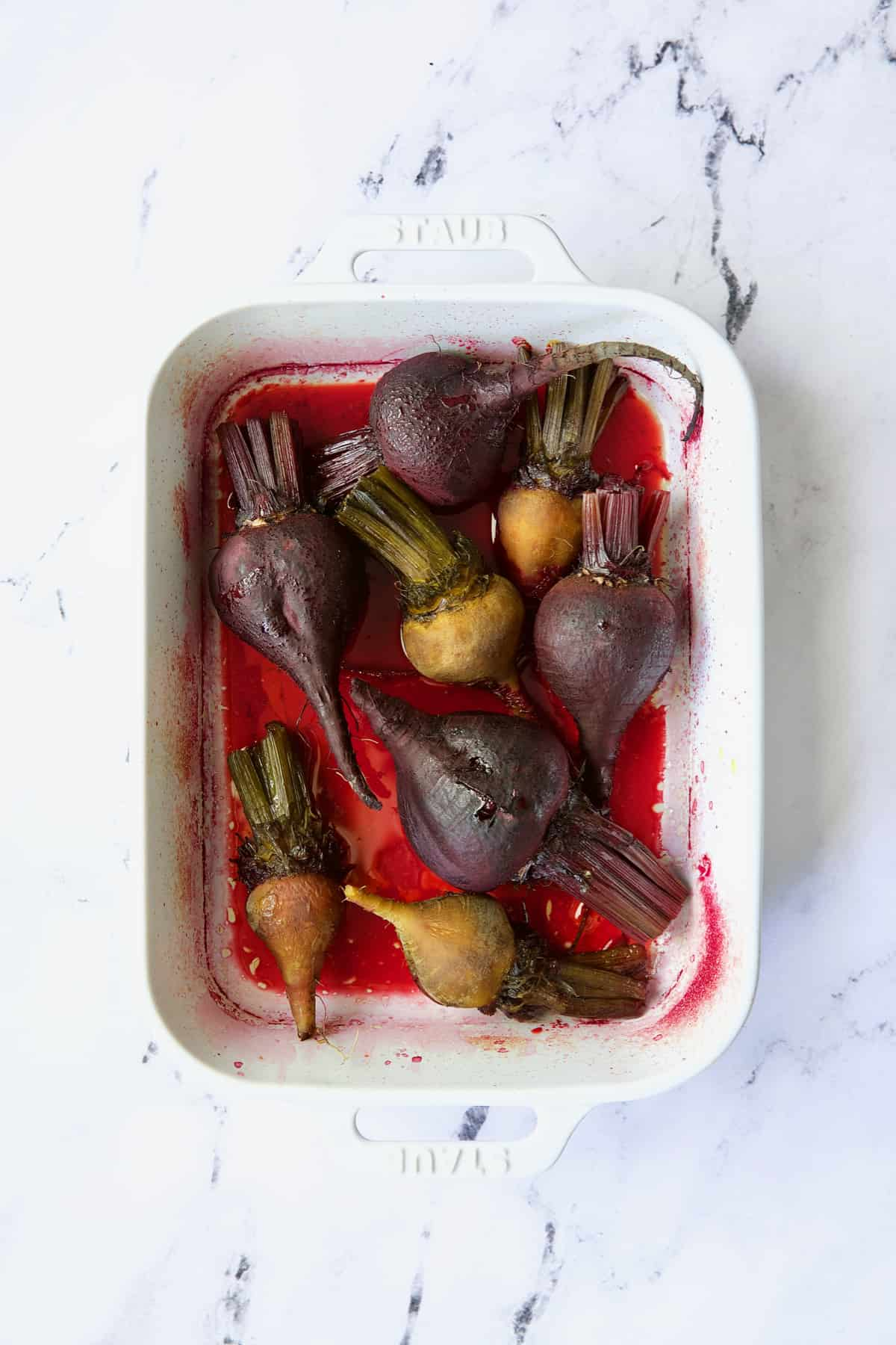 Roasted red and yellow beets in white baking dish.