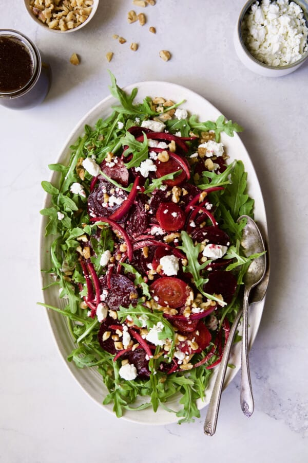 Photo of Roasted Beet Salad with Walnuts Goat Cheese and Honey Balsamic Dressing on gray background with dressing, walnuts and goat cheese in small bowls.