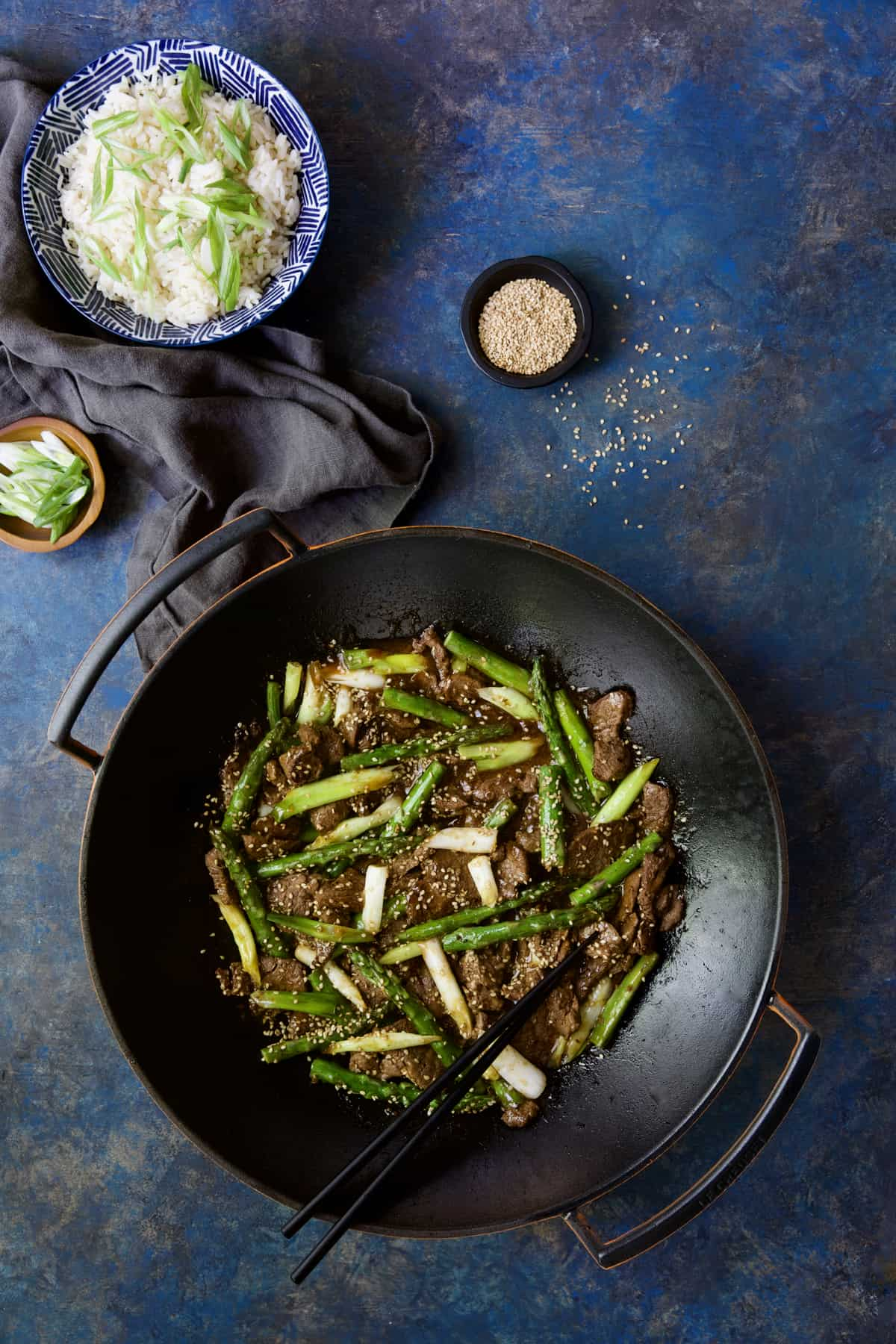 Sesame Beef and Asparagus Stir-Fry with bowl of rice and small bowls of scallions and sesame seeds.