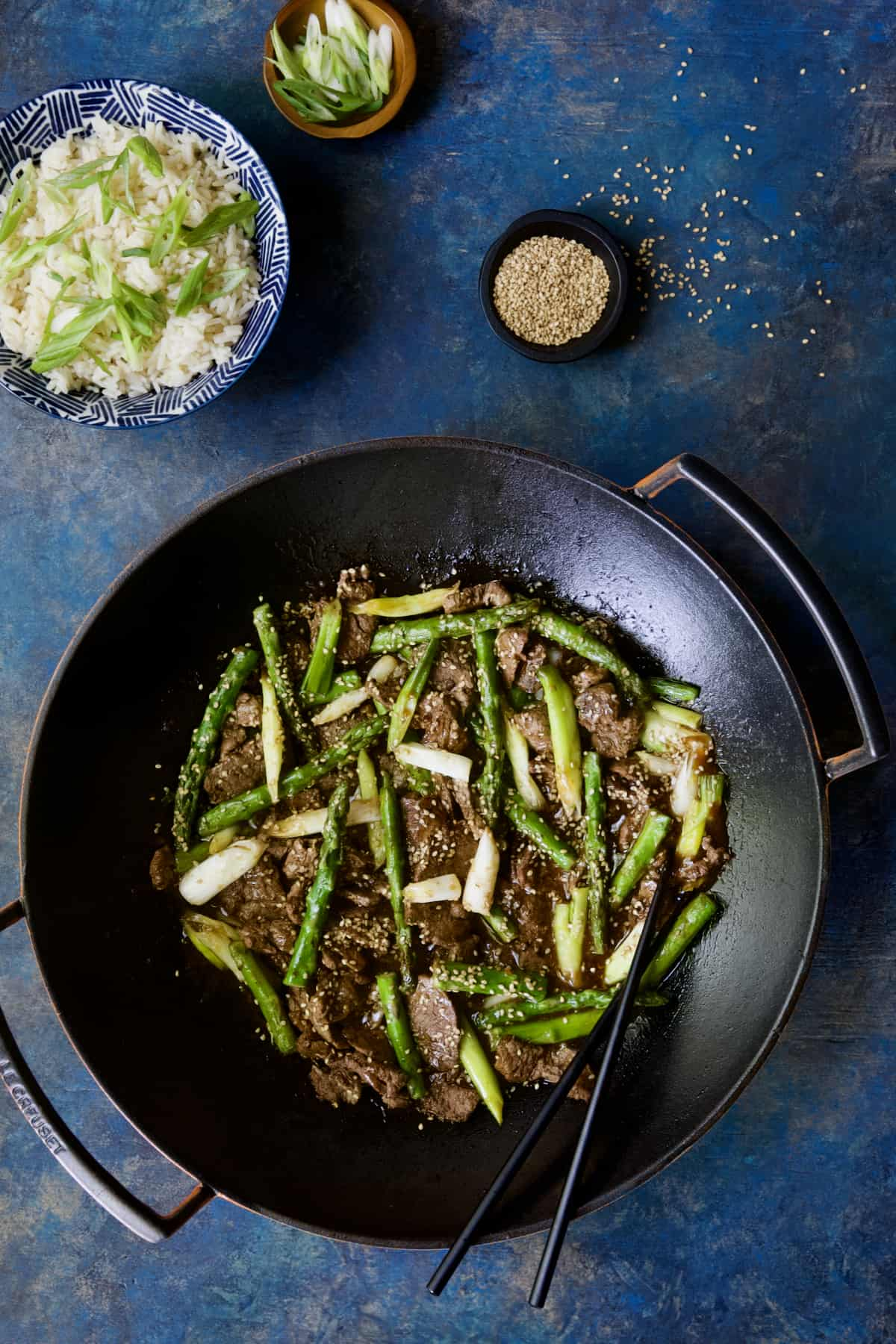 Photo of Sesame Beef and Asparagus Stir-Fry in cast iron wok on bright blue background.