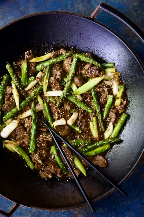 Close-up photo of Sesame Beef and Asparagus Stir-Fry in cast iron wok.