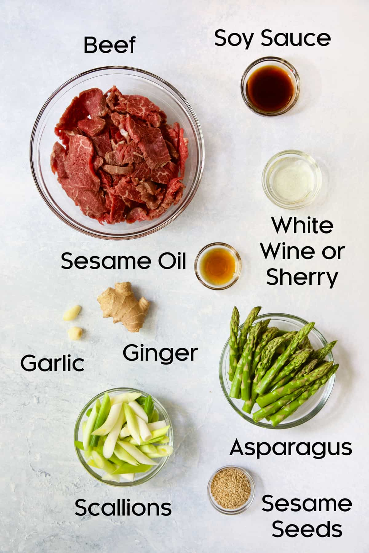 Ingredients for Sesame Beef and Asparagus Stir-Fry in glass bowls.