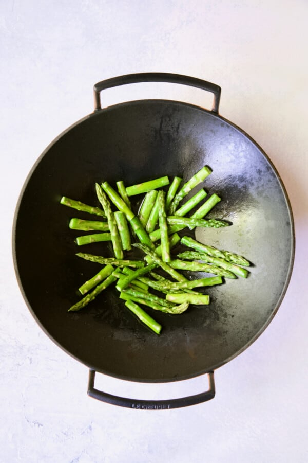 Process photo of asparagus being cooked in cast iron wok.