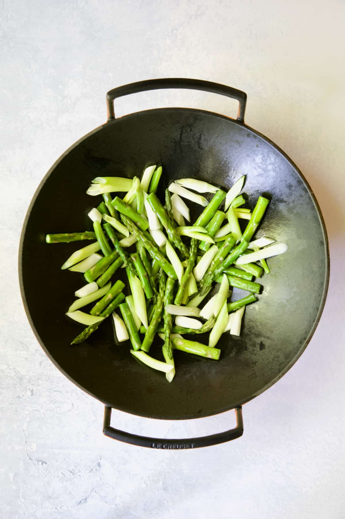 Asparagus and scallions in cast iron wok.