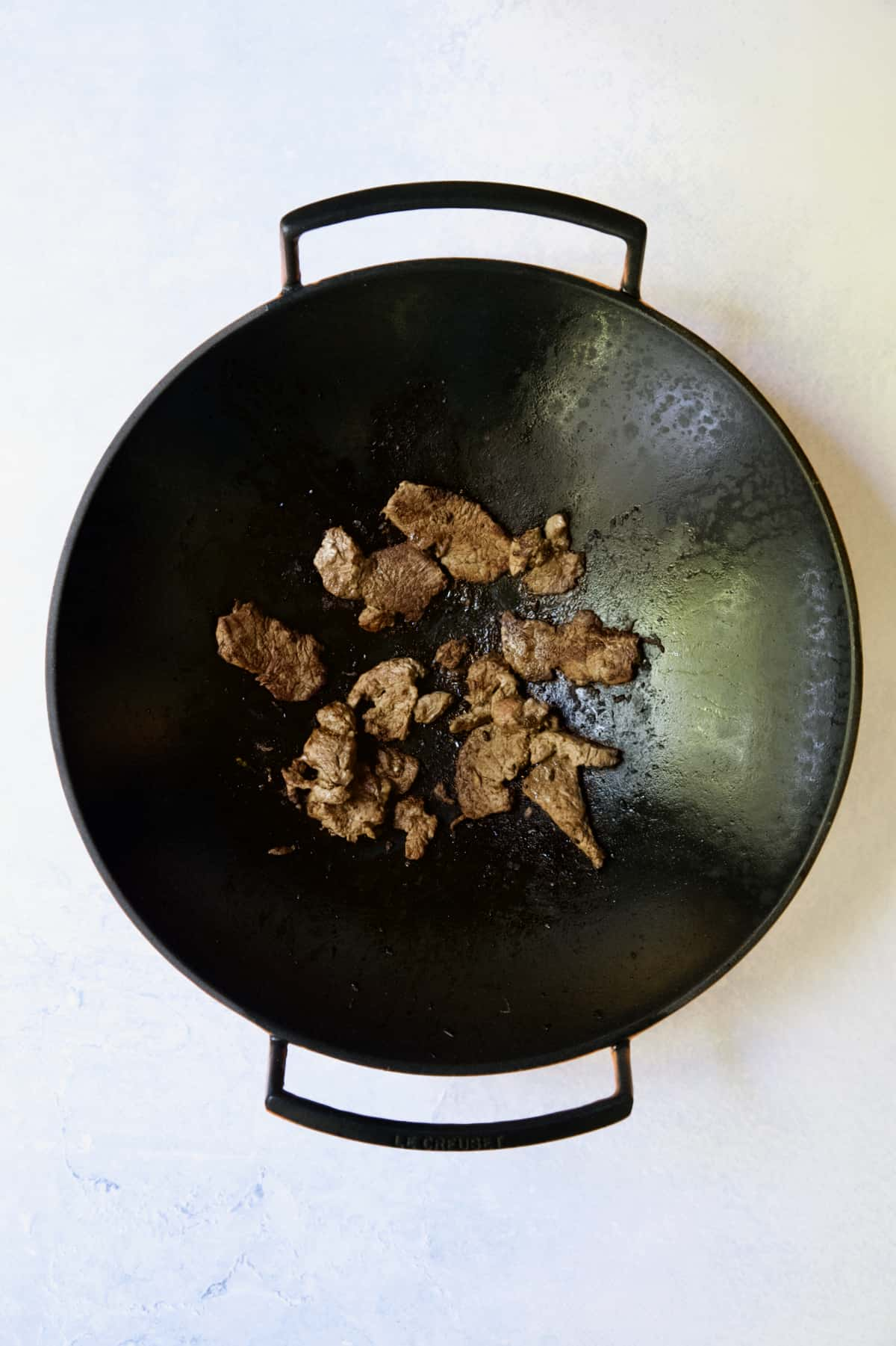 Beef being browned in cast iron wok.