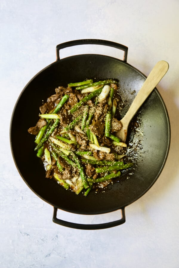 Process photo of Sesame Beef and Asparagus Stir-Fry being stirred with wooden spoon.
