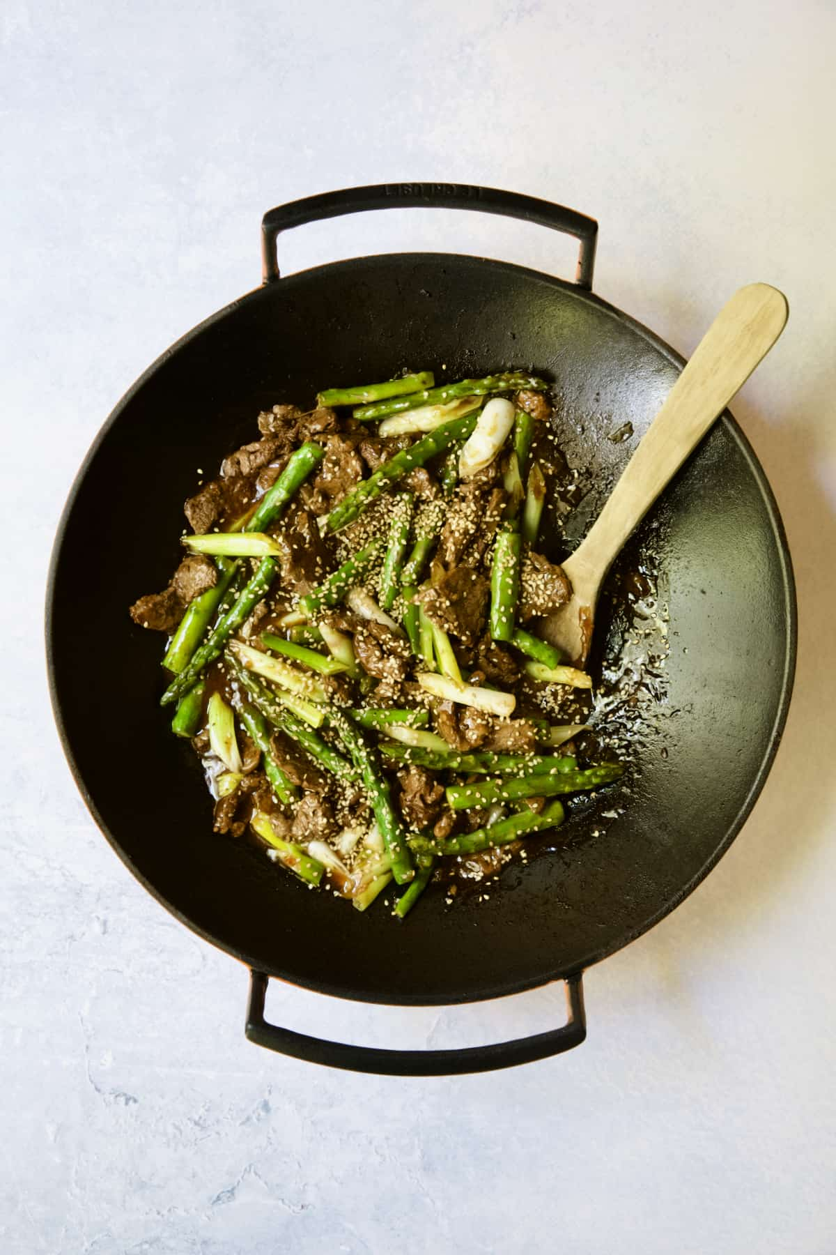 Sesame Beef and Asparagus Stir-Fry being stirred with wooden spoon.