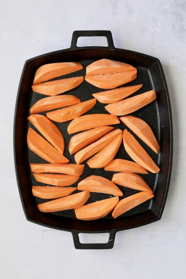Photo of sweet potato wedges on cast iron pan before being roasted.