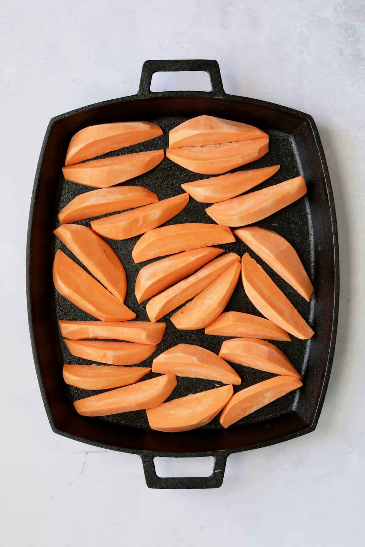 Sweet potato wedges on cast iron pan before being roasted.