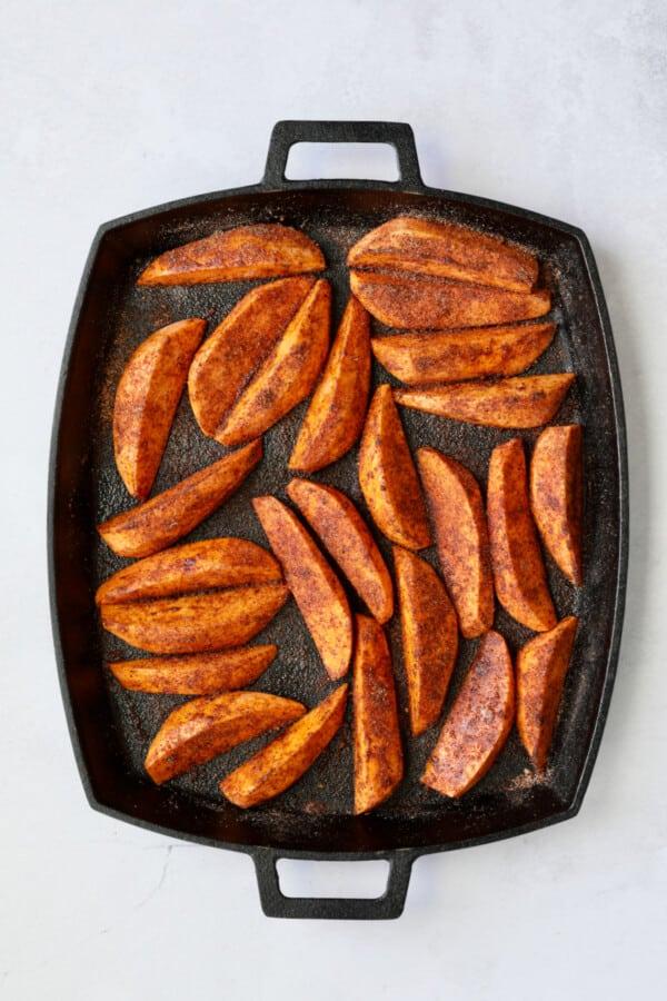 Photo of Southwestern Sweet Potato Wedges on cast iron pan with seasoning mix before being roasted.