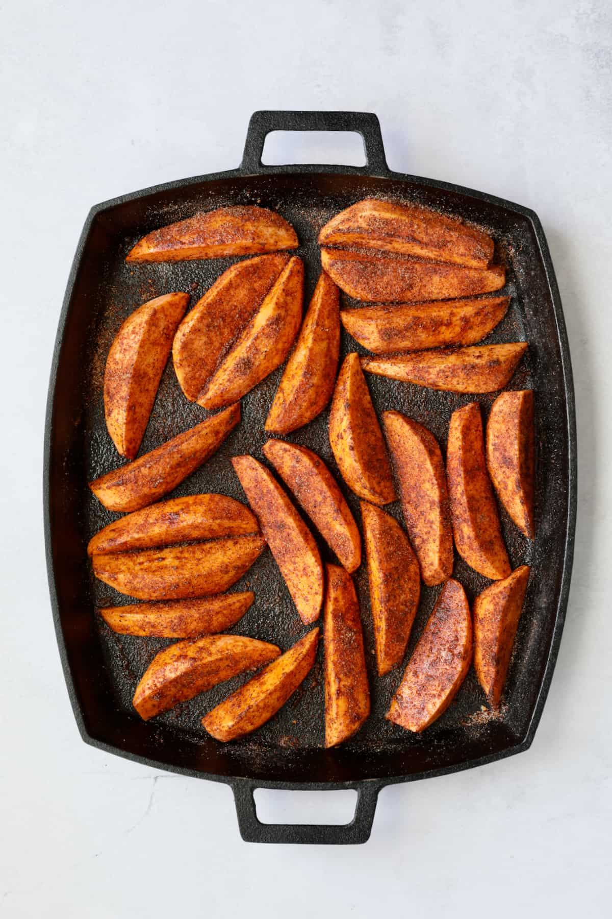 Southwestern Sweet Potato Wedges on cast iron pan with seasoning mix before being roasted.