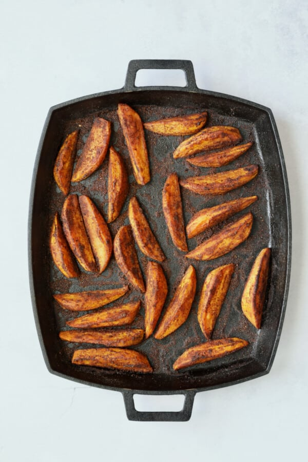 Photo of Southwestern Sweet Potato Wedges on cast iron pan after being roasted.