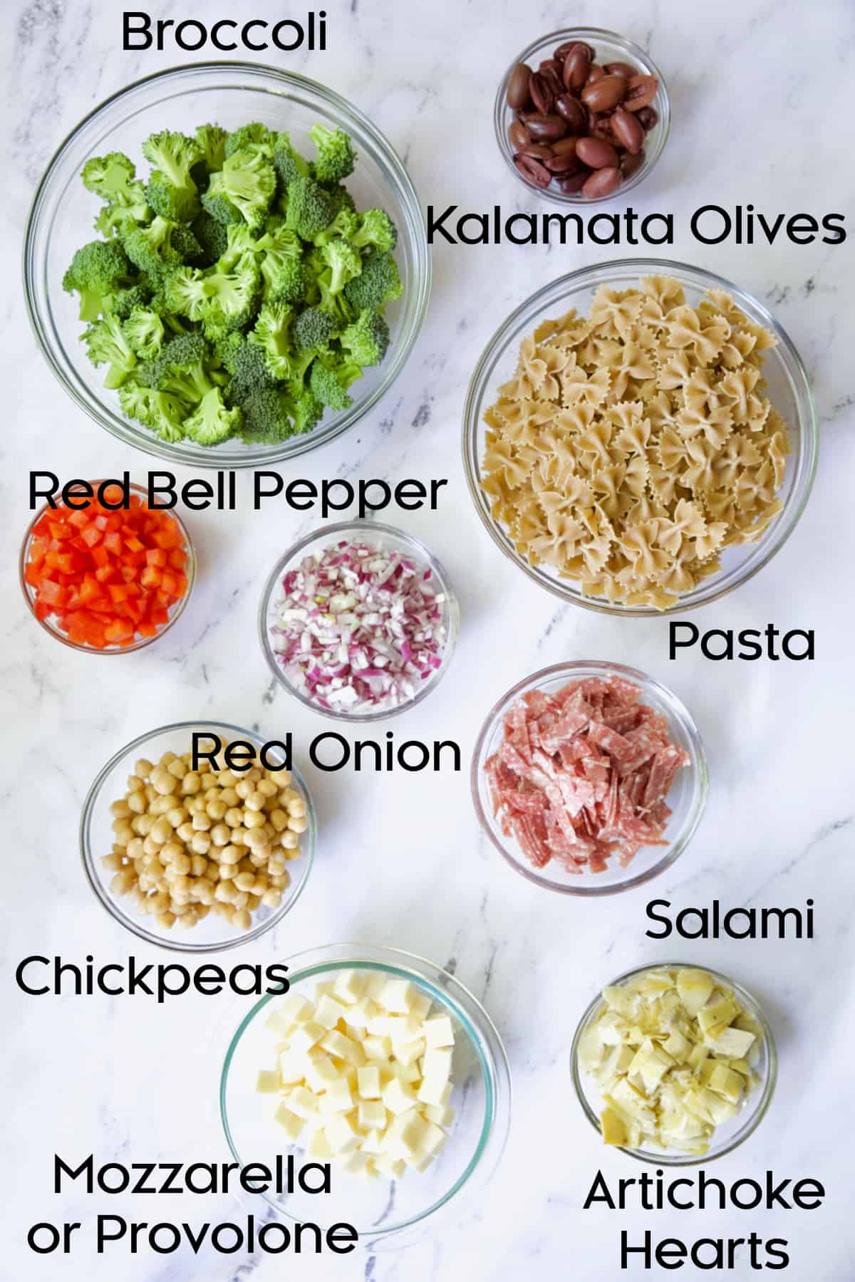 Ingredients for Antipasto Pasta Salad in glass bowls.