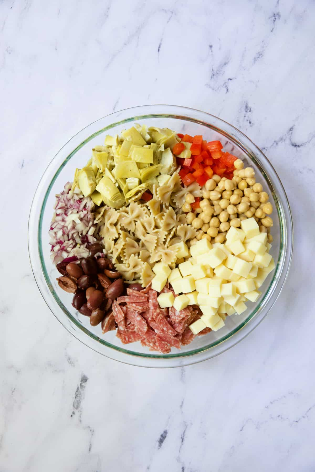 Ingredients for Antipasto Pasta Salad with Parmesan Herb Vinaigrette in glass bowl before being combined.
