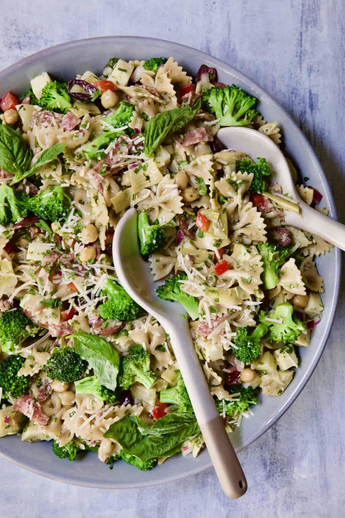 Antipasto Pasta Salad with Parmesan Herb Vinaigrette garnished with fresh basil.
