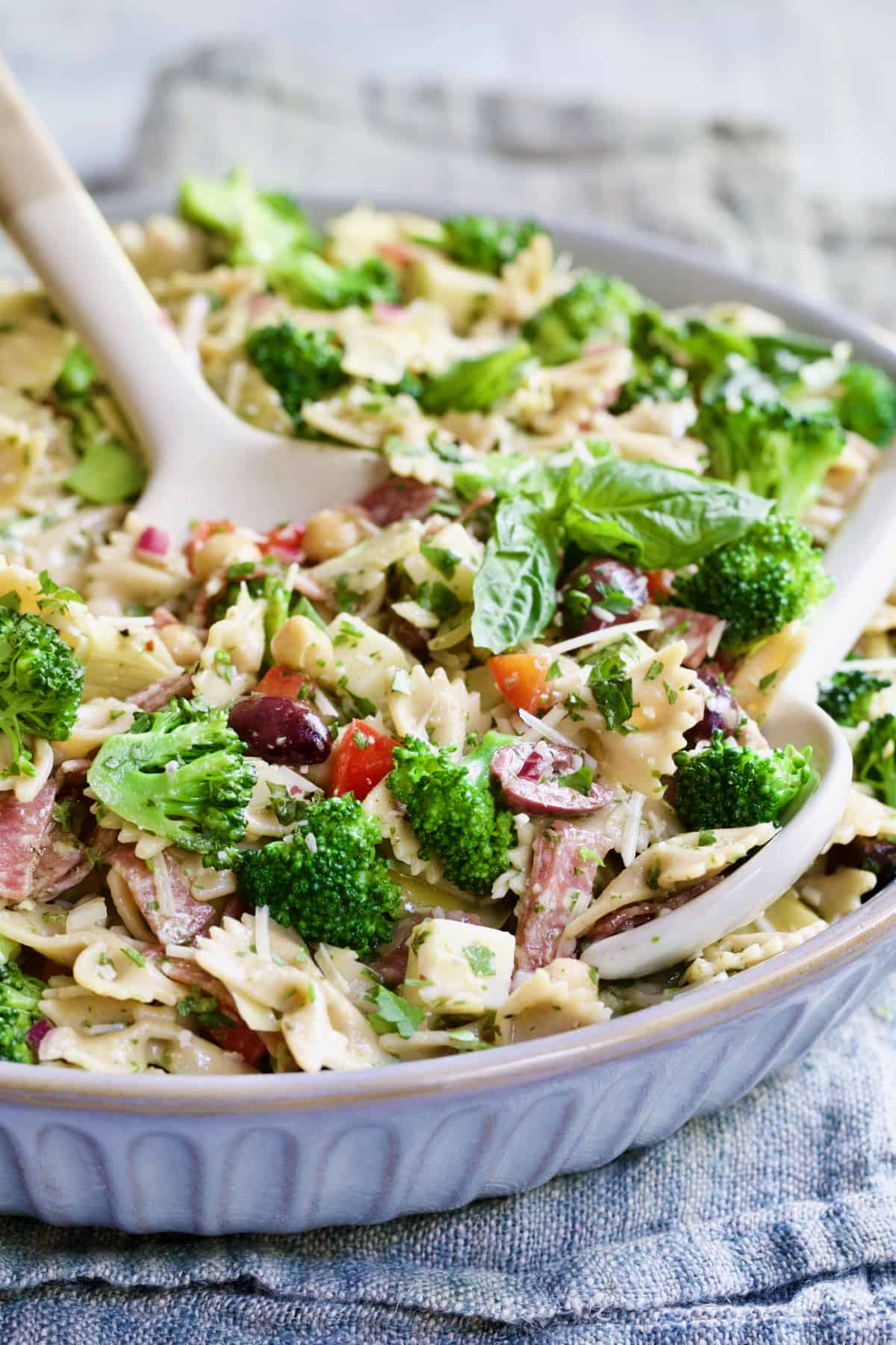 Close-up of Antipasto Pasta Broccoli Salad with Parmesan Herb Vinaigrette with serving utensils in gray bowl.