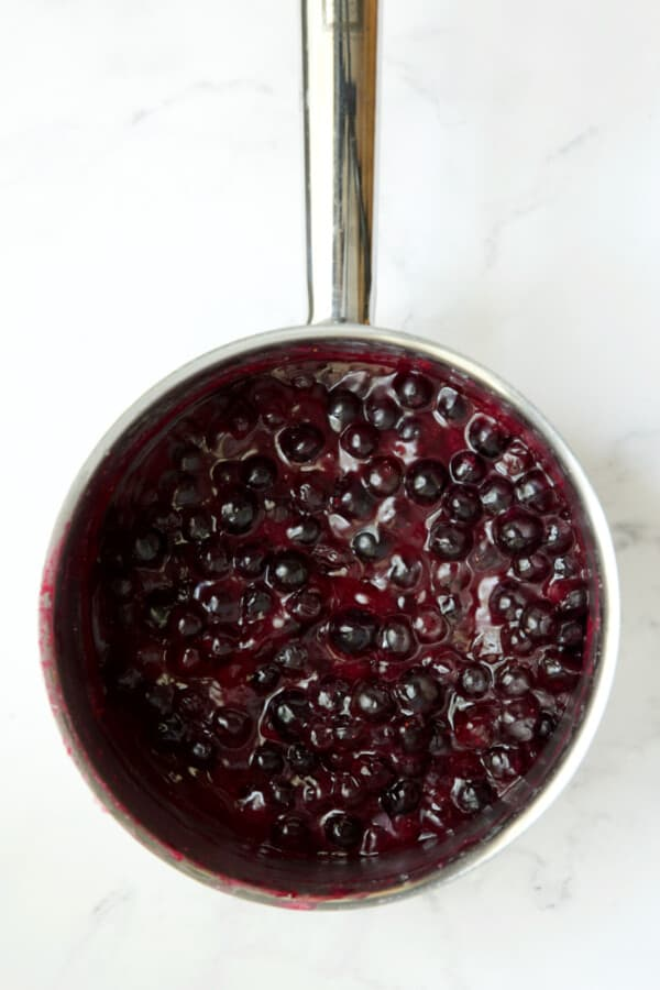 Process photo of blueberries in stainless steel saucepan.