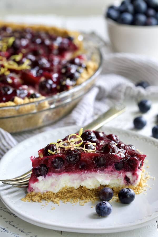 Photo of a slice of Blueberry Cream Cheese Pie on a white plate.