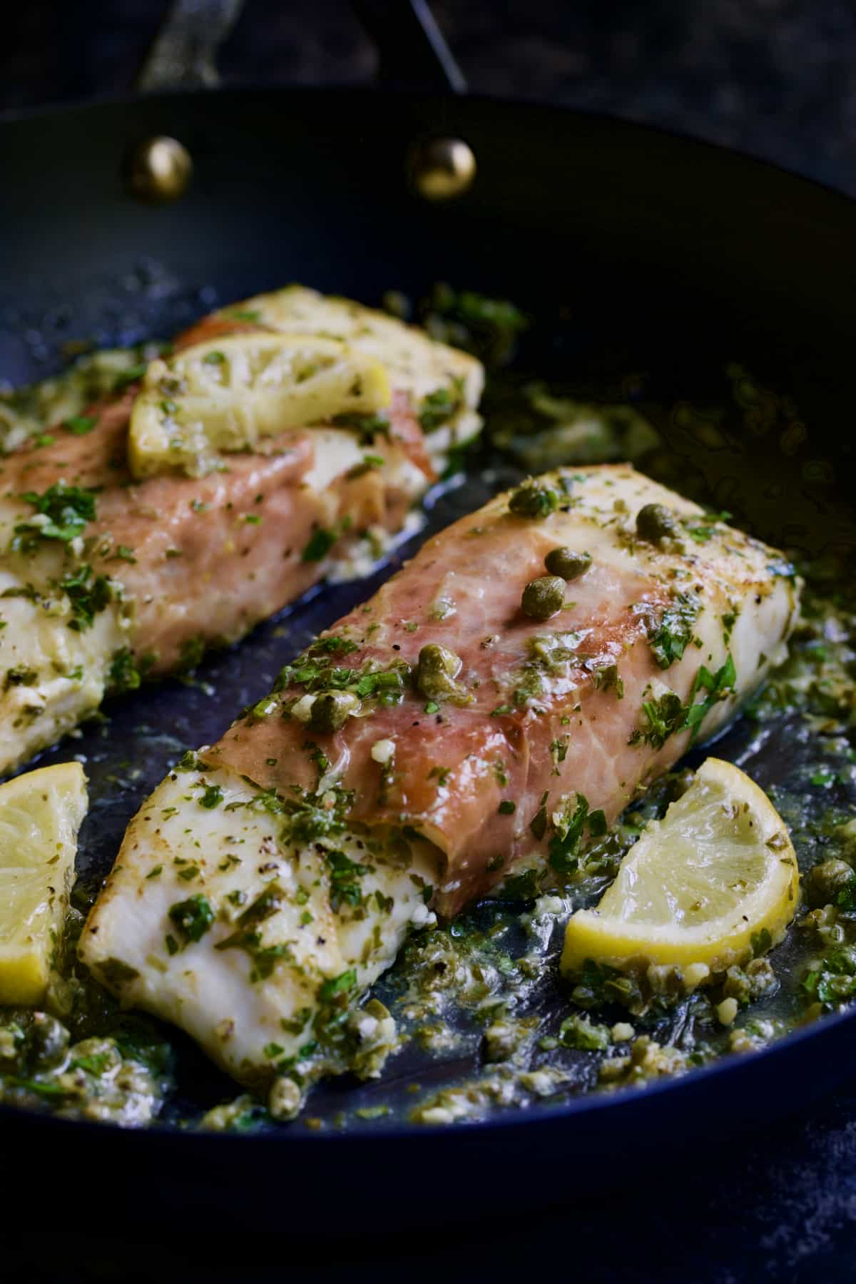 Prosciutto-Wrapped Halibut with Herb - Caper Butter with lemon wedges in black skillet.