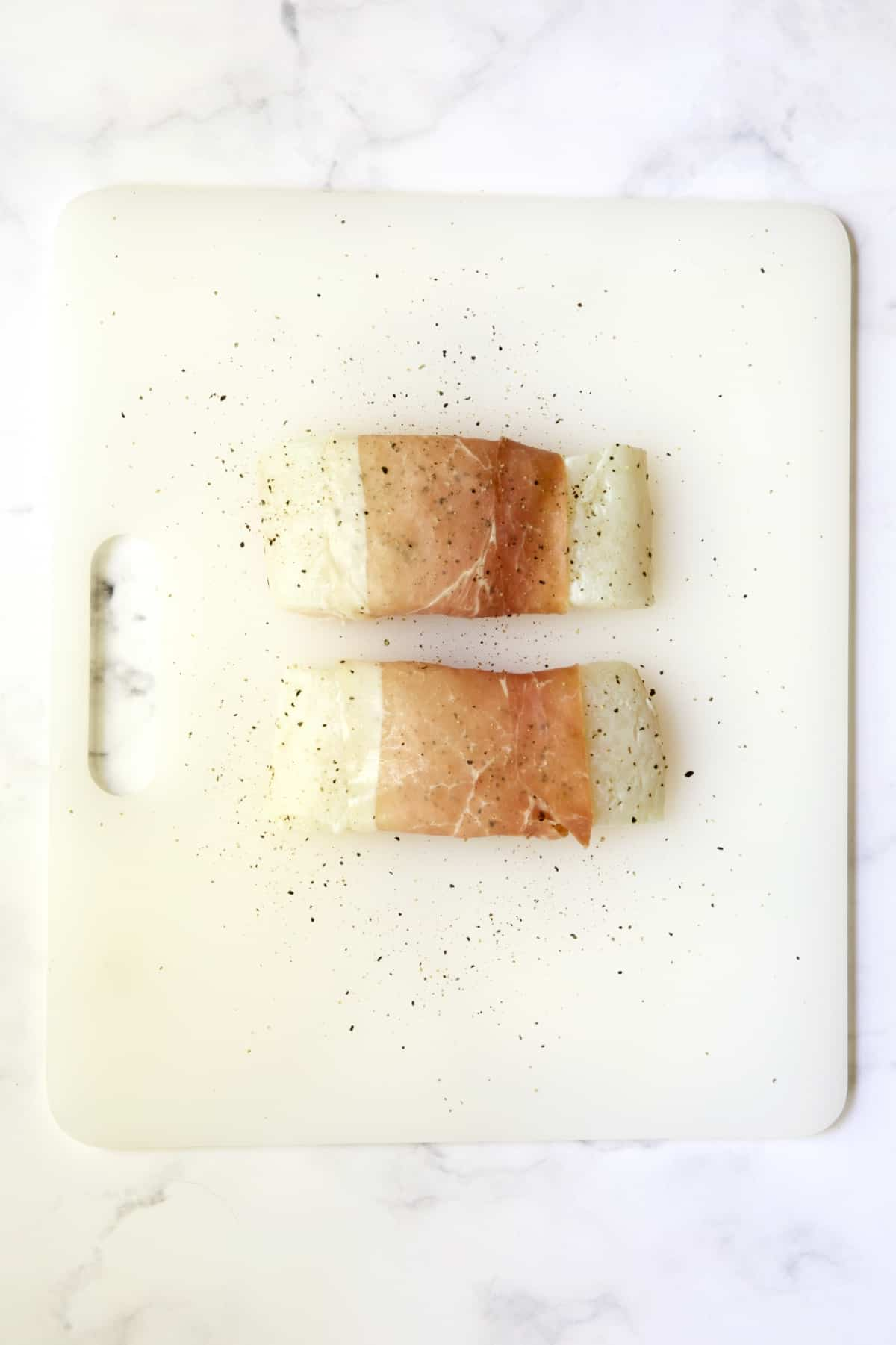 Two prosciutto-wrapped halibut fillets seasoned with pepper on a white plastic cutting board before being cooked.