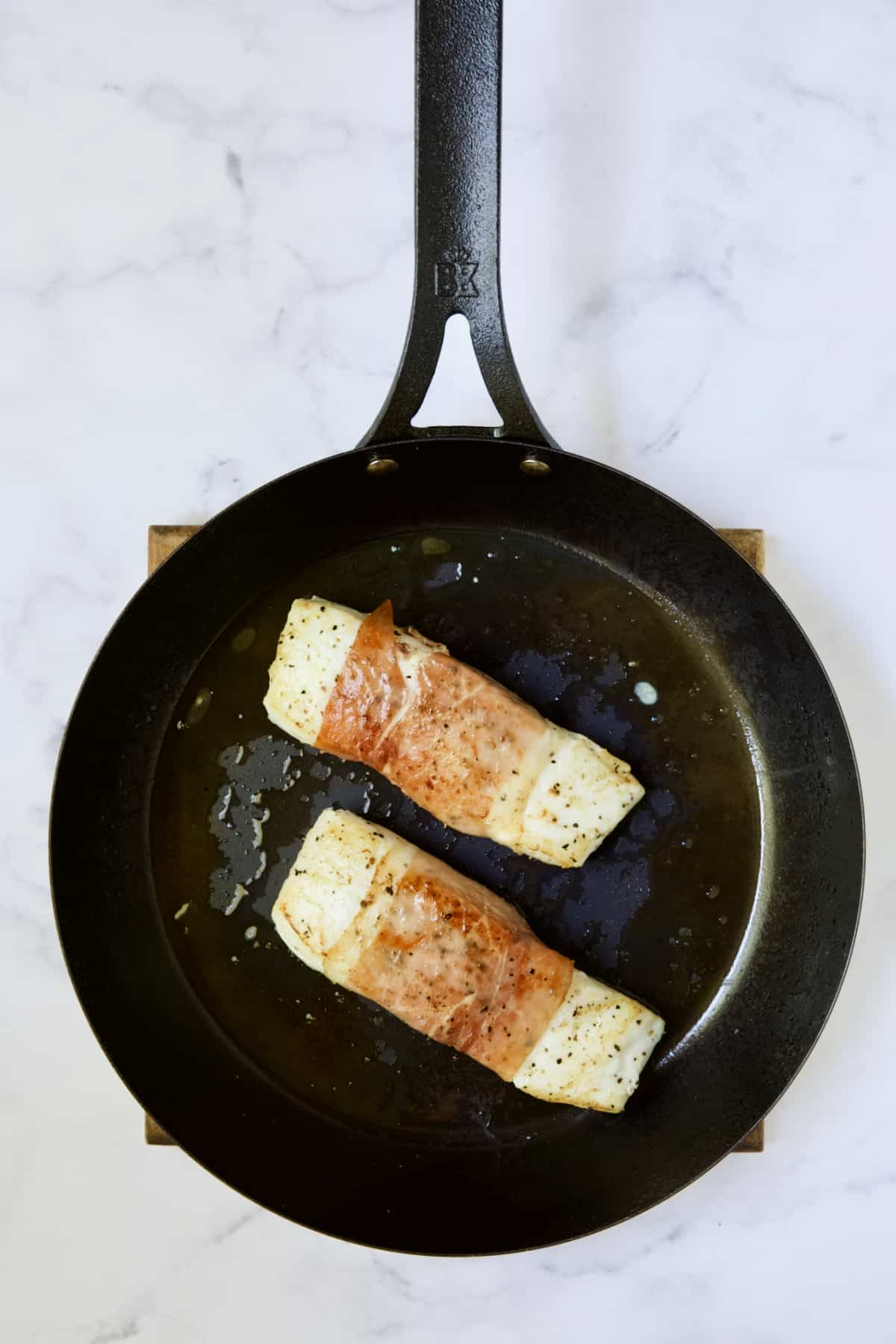Two prosciutto-wrapped halibut fillets in black skillet being browned.