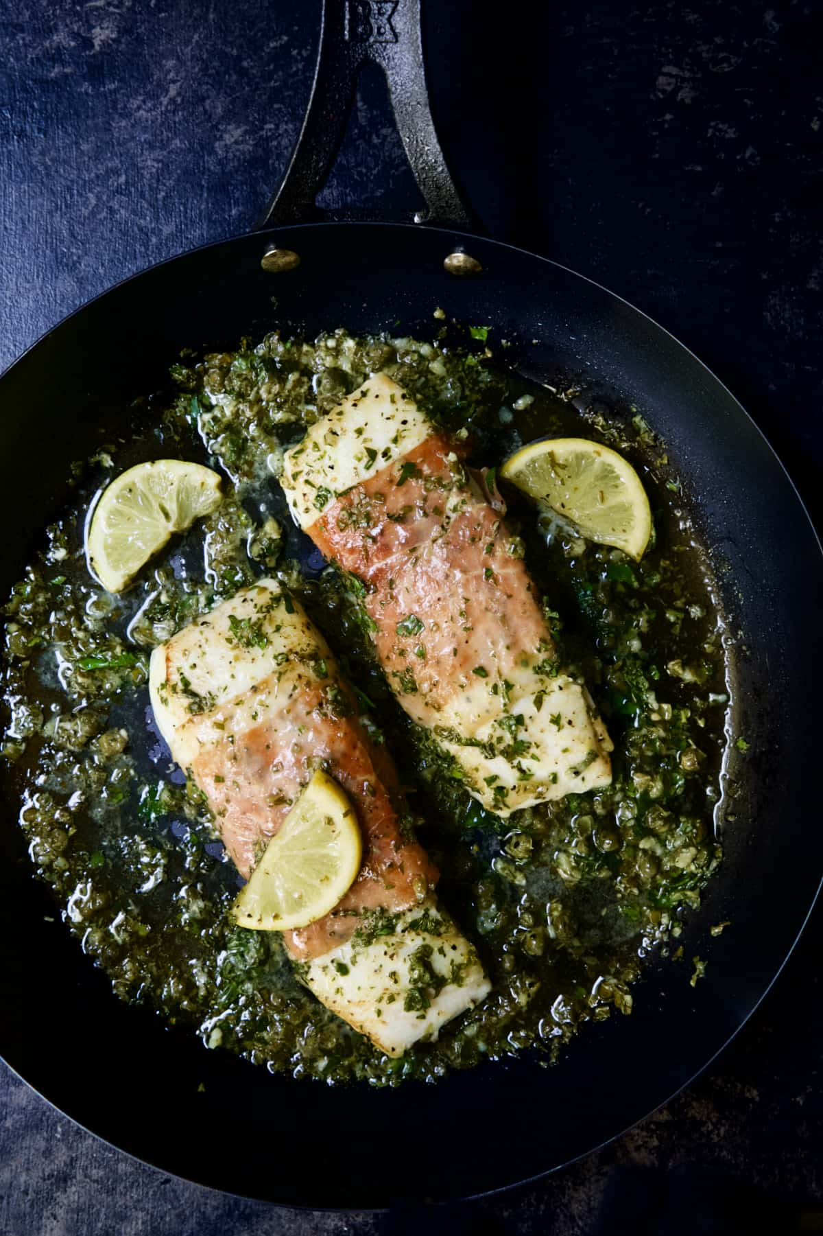 Prosciutto-Wrapped Halibut with Herb - Caper Butter in black skillet with lemon wedges.