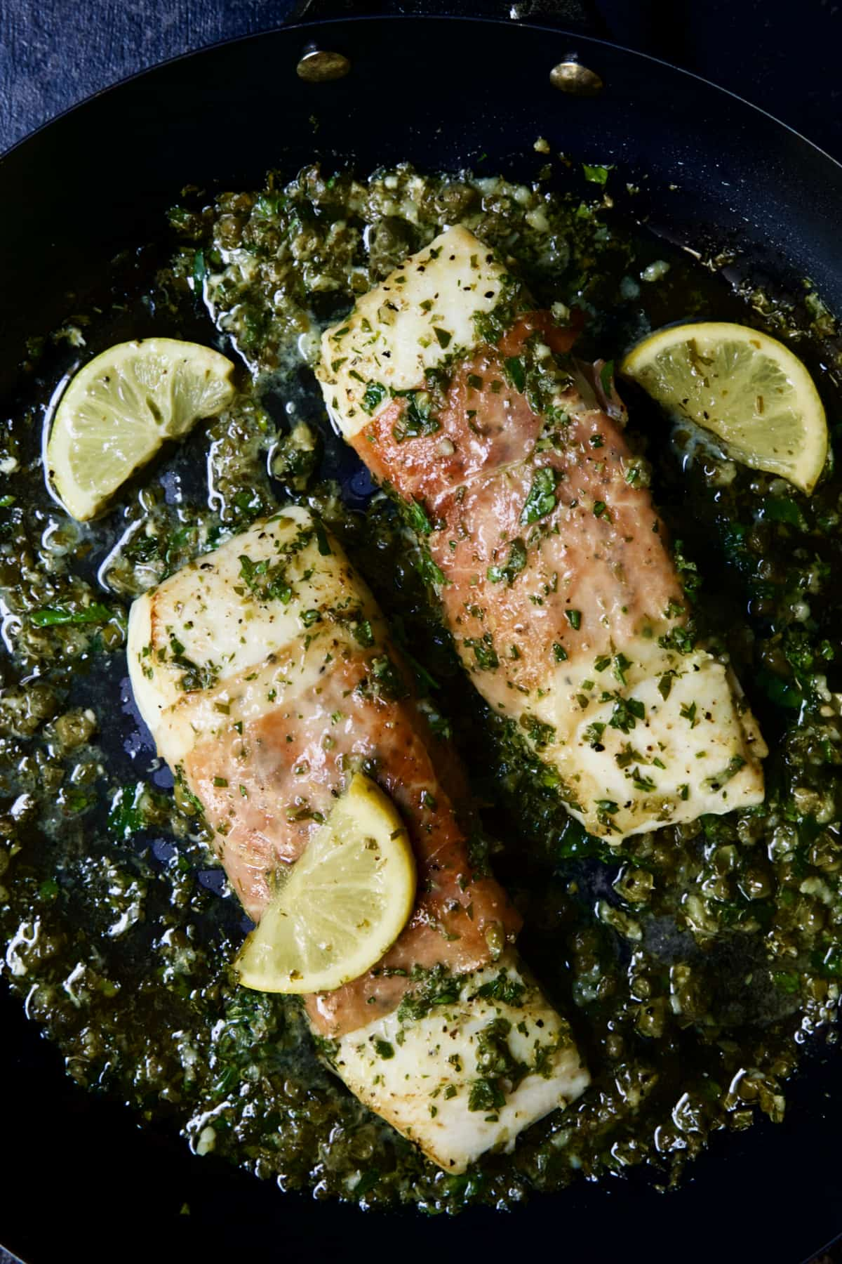 Prosciutto-Wrapped Halibut with Herb - Caper Butter with lemon wedges.