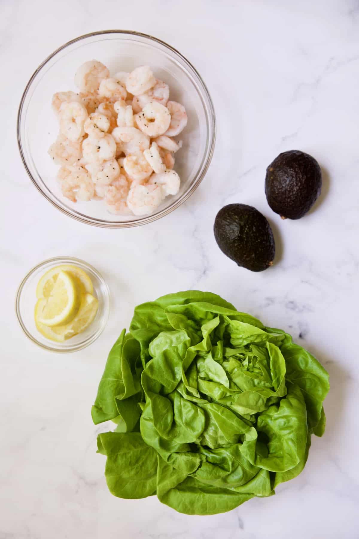Cooked shrimp, lemon wedges, avocados and lettuce.