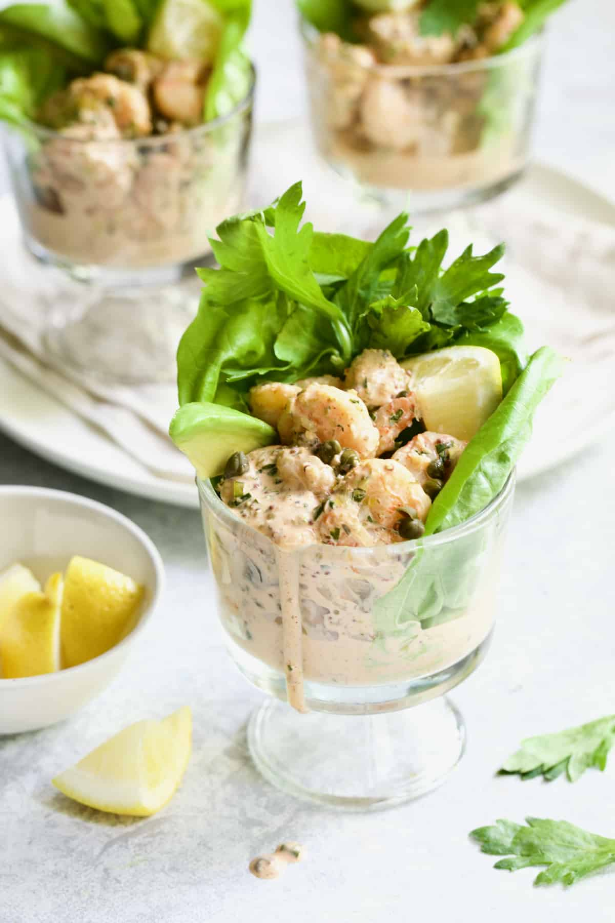 Sriracha Shrimp Remoulade Cocktail with lemon wedge and celery leaves.