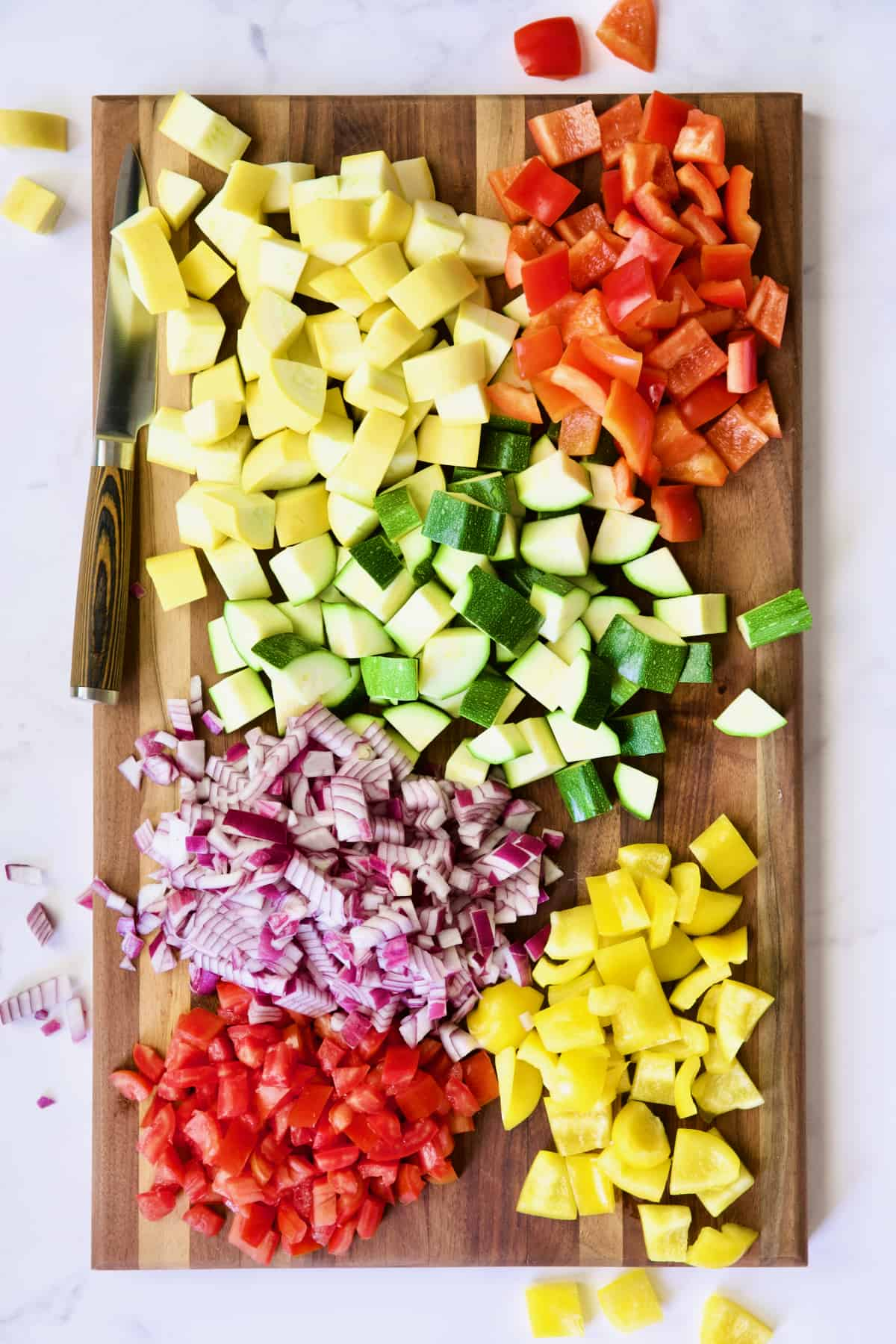 Cut-up vegetables for ratatouille on dark wood cutting board.
