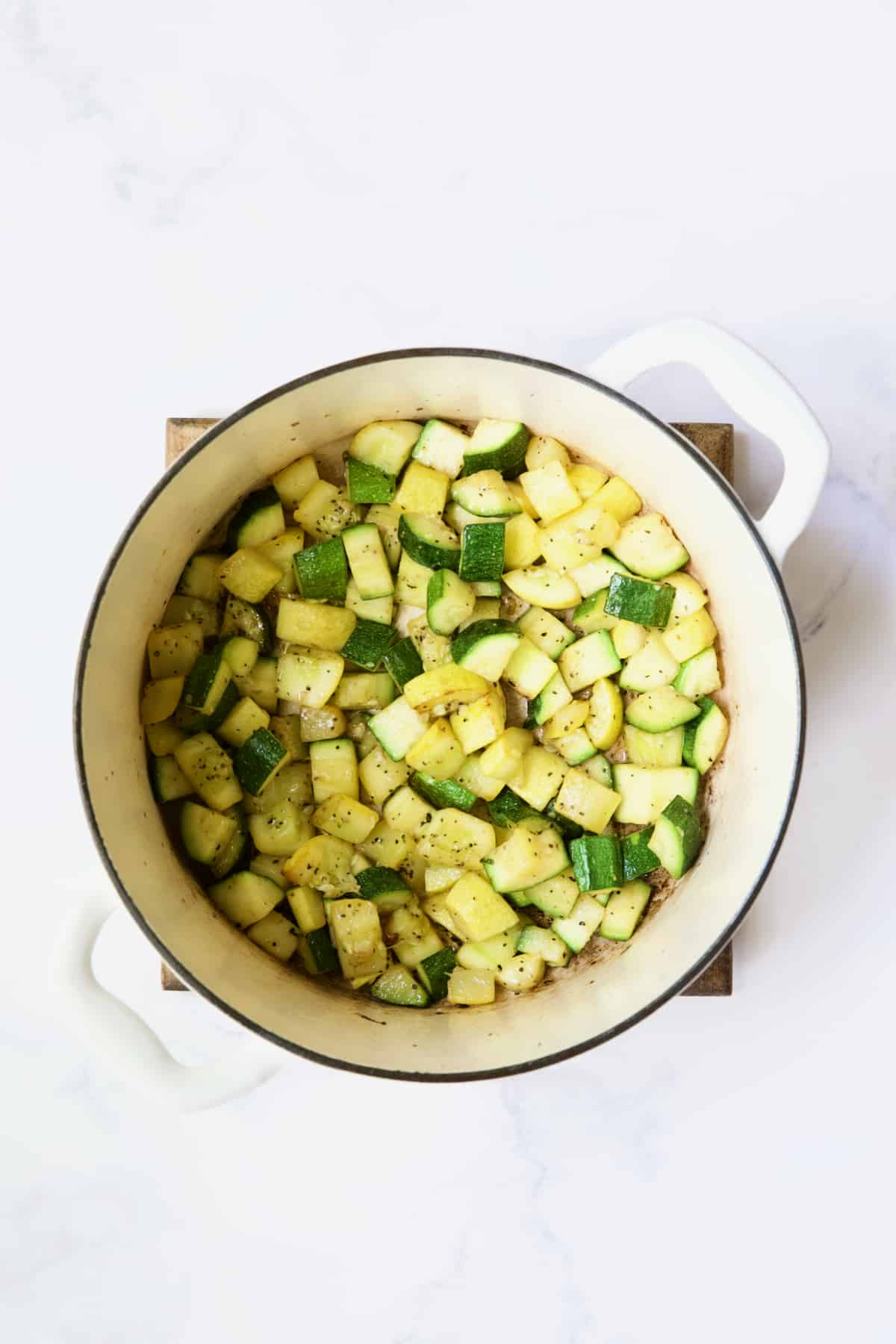 Process photo of zucchini and yellow squash being cooked in white Dutch oven.