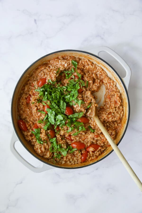 Process photo of farro risotto after basil is added.