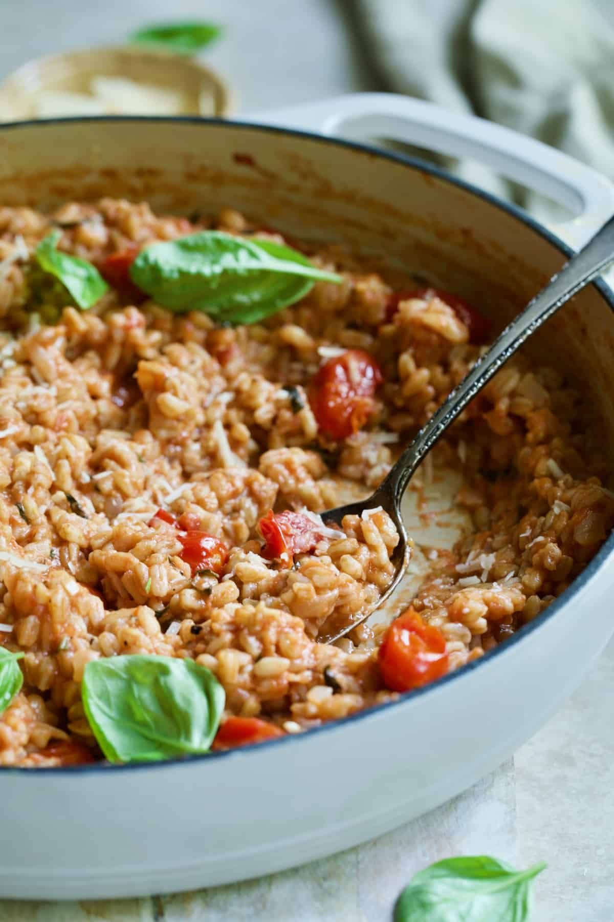 Tomato Farro Risotto with Basil and Parmesan in white cast iron skillet with serving spoon.