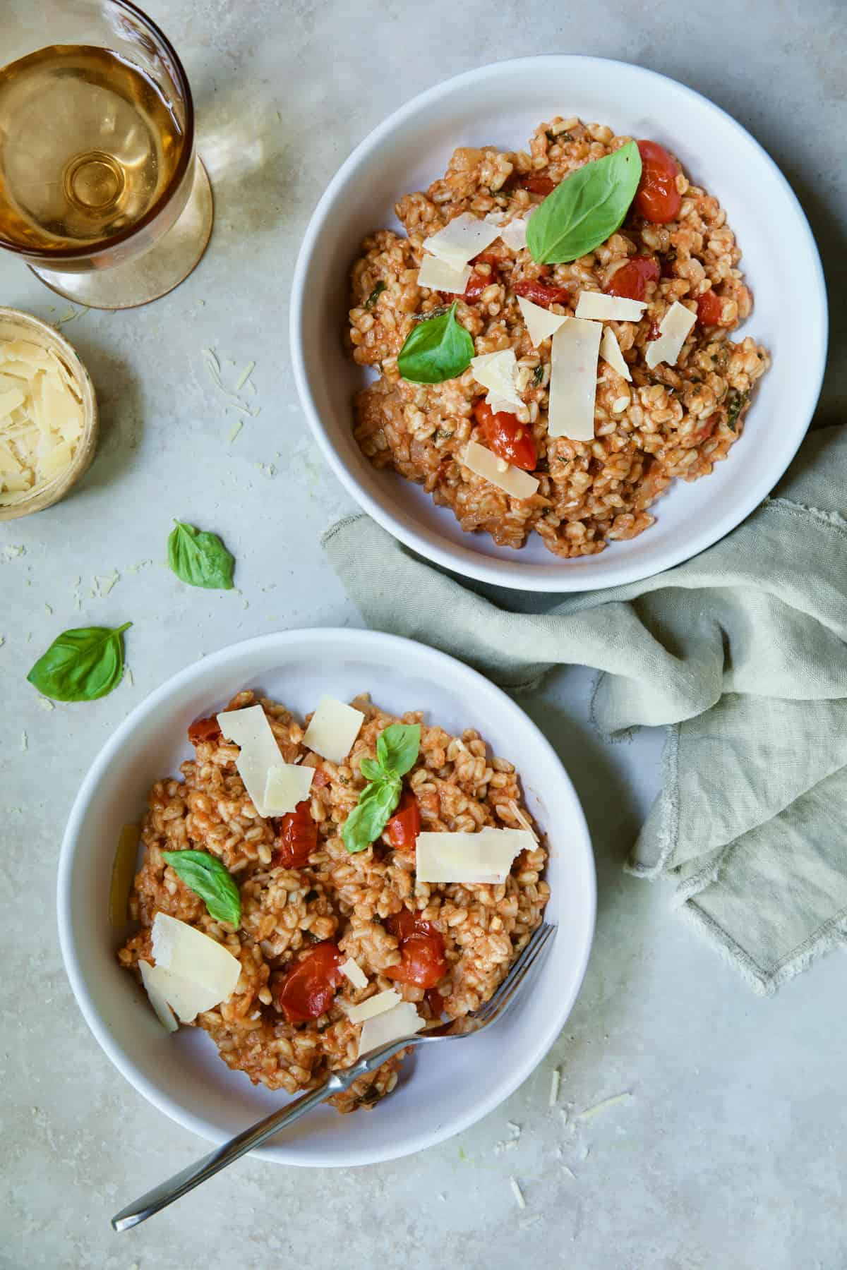 Two servings of Tomato Farro Risotto with Basil and Parmesan in white bowls garnished with basil leaves.