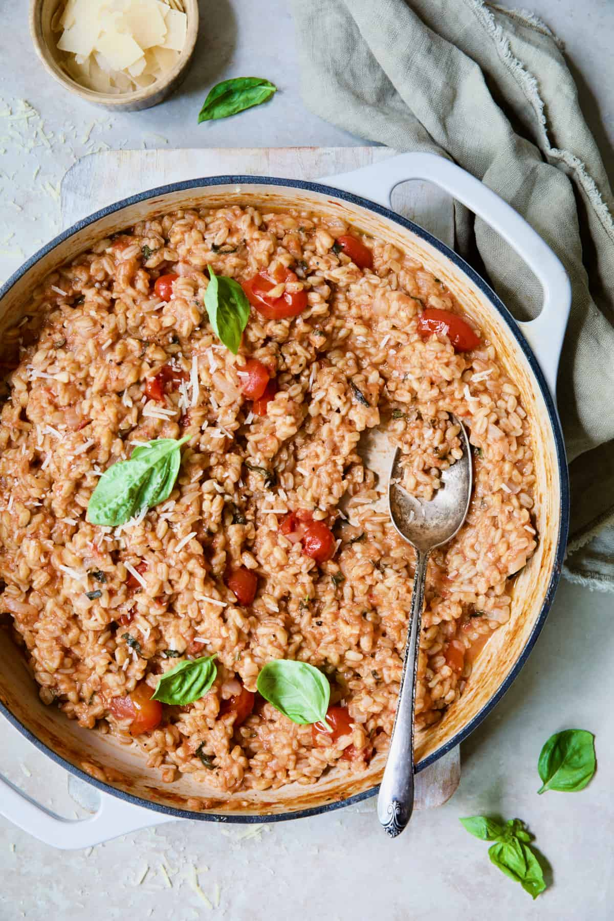 Tomato Farro Risotto with Basil and Parmesan in white enameled cast iron skillet garnished with fresh basil.